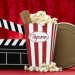 a bag of popcorn, black clapper board, a golden film can and cinema tickets with red background