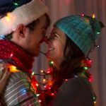Romantic young couple wrapped in decorative lights at christmas